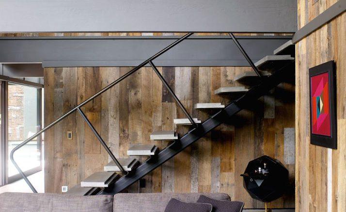 O mobiliário moderno faz contraste com a madeira usada das paredes. Sob a escada, um bar diferente