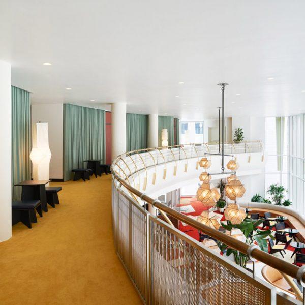 O hall de distribuição no mezanino recebe cortinas, poltronas em madeira e luminárias