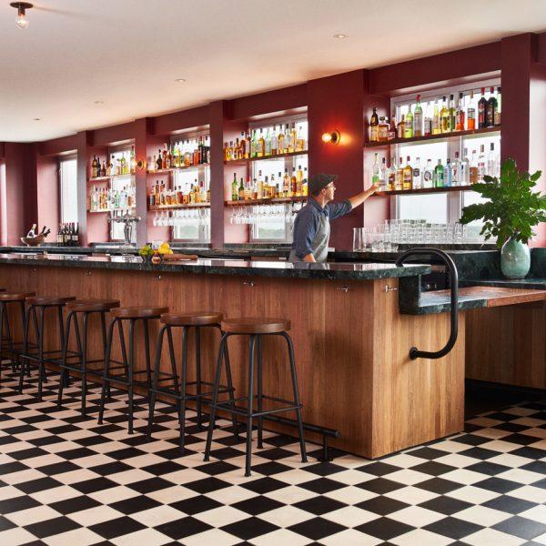 Um dos bares do hotel com piso P&B, balcão de madeira e vermelho como contraponto. Observe que atrás das prateleiras com garrafas, é possível ver as janelas da fachada