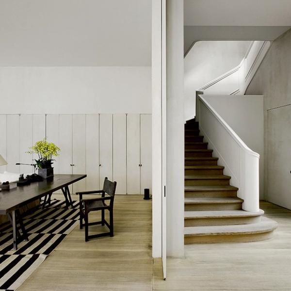 Hall de entrada e living de Vincent Van Duysen. Ao fundo, portas camarão isolam/integram a cozinha