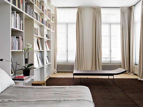 O quarto enorme acomoda os muitos livros do arquiteto. Observe como o tapete é do tamanho exato para receber também a chaise