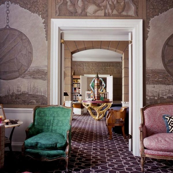 Mural pintado à mão inspirado em Constantinopla faz par com o tapete estampado com elos. Ashley assina a mesa dourada e o obelisco ao fundo