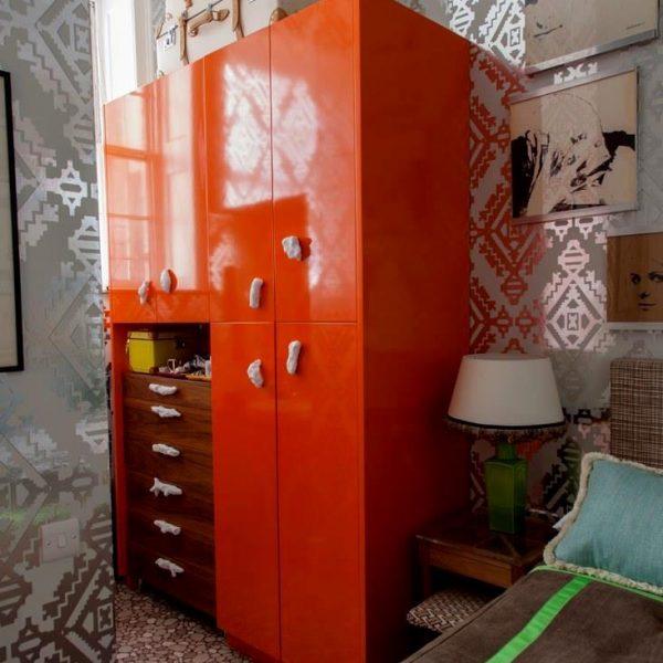 O armário  lindo em laca laranja recebeu puxadores dispostos em posições diferentes, em ótima solução para descontrair a decoração. Adorei!