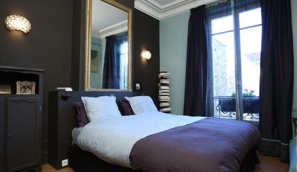 O quarto, de base preta e abundante luz natural. O móvel antigo pintado da cor da parede é solução perfeita para pequenos espaços