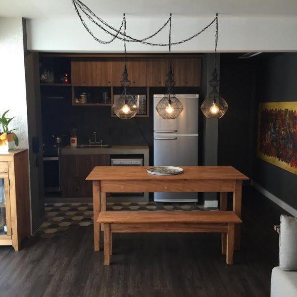 A mesa funciona como divisor entre a sala e a cozinha, e ao mesmo tempo é um ponto de atração