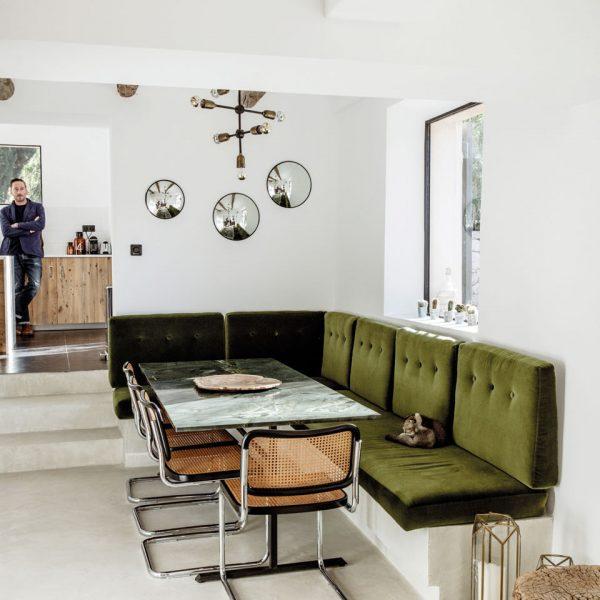 No jantar, o sofá em alvenaria recebeu almofadas verdes. Cadeiras Cesca, uma das minhas preferidas, assinadas por Marcel Breuer em 1929