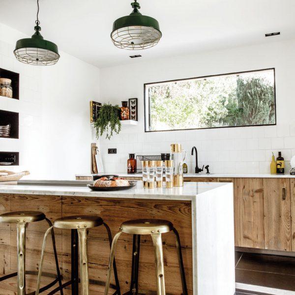 A madeira sem acabamento contribui para o clima rústico na cozinha. As linhas retas da bancada e o piso preto trazem o espaço para o século XXI