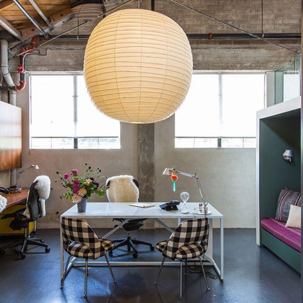 A sala de trabalho compartilhada conta com um sofá em rosa, tempero perfeito para movimentar a decoração. A luminária de inspiração japonesa é um item que faz diferença e tem baixo custo. No bairro da liberdade em São Paulo, você encontra em várias lojas. Dê preferência aos modelos sem estampas