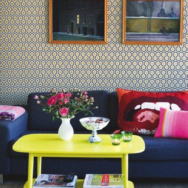A combinação com o amarelo e o rosa das almofadas deixa o sofá mais leve. O papel de parede ocupa lugar importante no todo, e pode ser substituído por carimbos que você mesmo pode fazer com EVA e aplicar sobre uma cor bacana