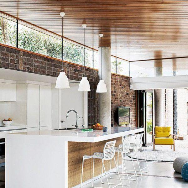 O balcão generoso acomoda eletros e também funciona como apoio, e o teto em madeira deixa o espaço mais nobre. Claro que quem tem esse tipo de cozinha deve pensar em uma churrasqueira para bifes e afins