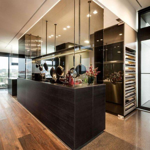 Inspirada nas cozinhas de restaurante, essa cozinha ficou bem moderna e está integrada mas isola os odores em função do vidro