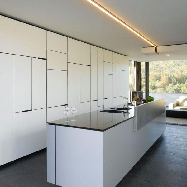 Os recortes das portas dos armários faz desenho moderno e movimenta a cozinha branca. Luminária para lá de linda!!
