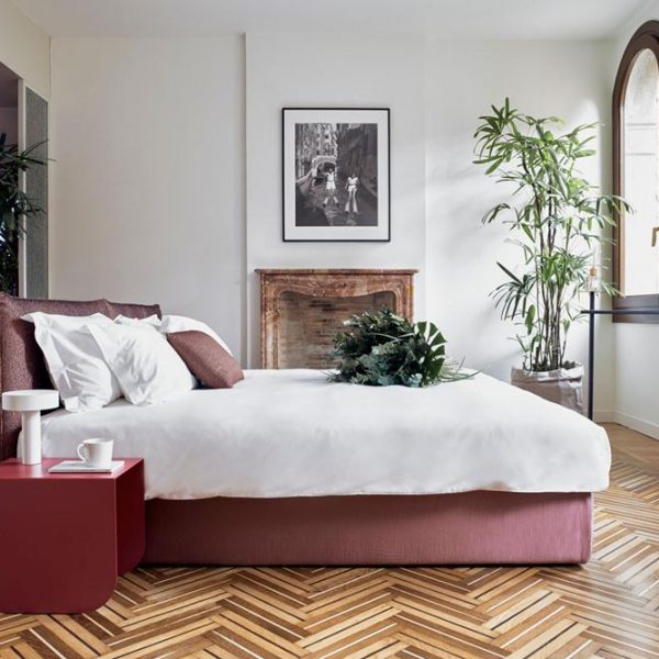 O quarto amplo tem piso em madeira, maravilhoso, e cama revestida em tecido vermelho/rosa, que lembra uma das cores mais vistas na cidade