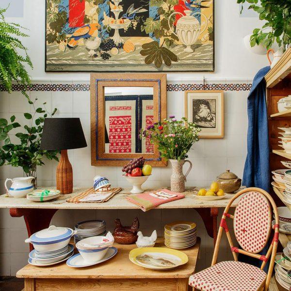 Louças de procedências diversas na cozinha em companhia de arte e cadeira de bistrô parisiense