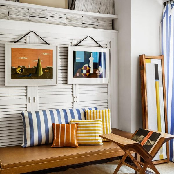 As listras das almofadas fazem ótima parceria com as formas do armário. Litografias de Picart Le Doux
