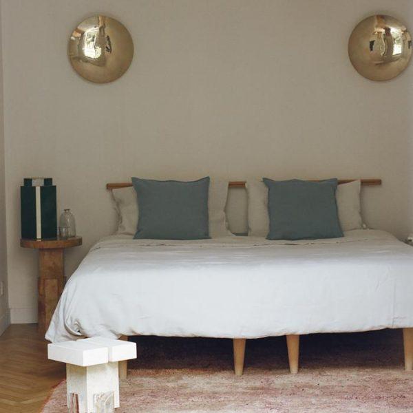 Luminárias espelhadas sobre cama desenhada por Nicholas, que também assina o banco de mármore. Tapete berbere