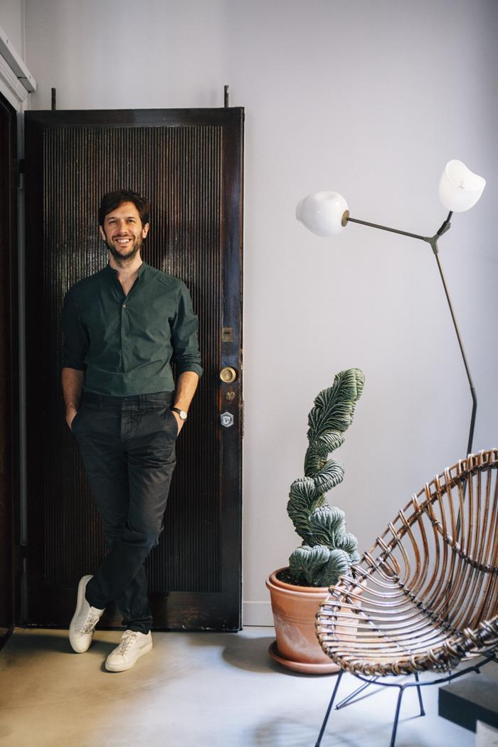 Na entrada do apartamento, Nicolas Bellavance-Lecompte faz pose pose ao lado de luminária Lindsey Adelman e poltrona em fibra de Franco Albini