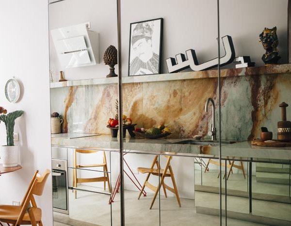 Armários espelhados e cadeiras dobráveis dos anos 1950 de Egon Eiermann, na cozinha para lá de linda do apartamento milanês