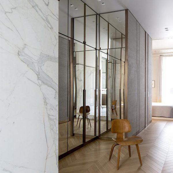 O closet, lindo, traz portas espelhadas e estrutura das portas em latão.
