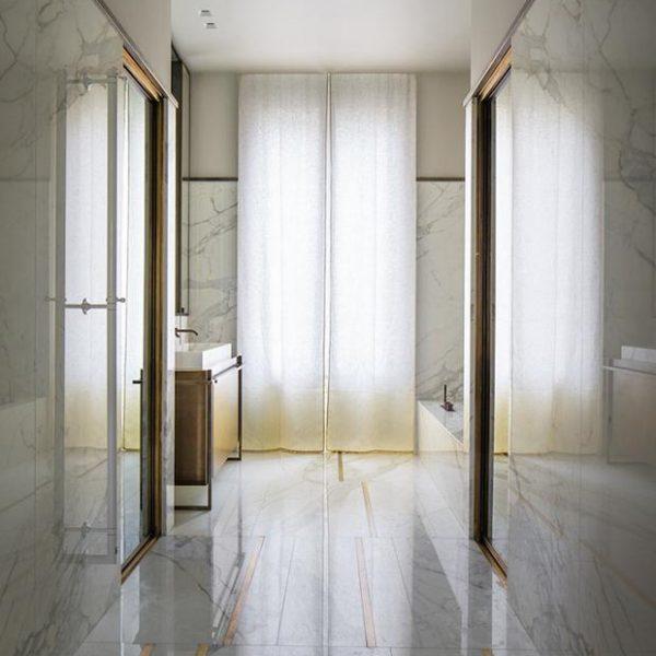 Mármore calacatta e latão no piso, cortina bem simples e corretíssima e linhas puras no projeto de Rodolphe Parente. Observe o acabamento do mármore, um filete mais escuro e tinta na parte superior.