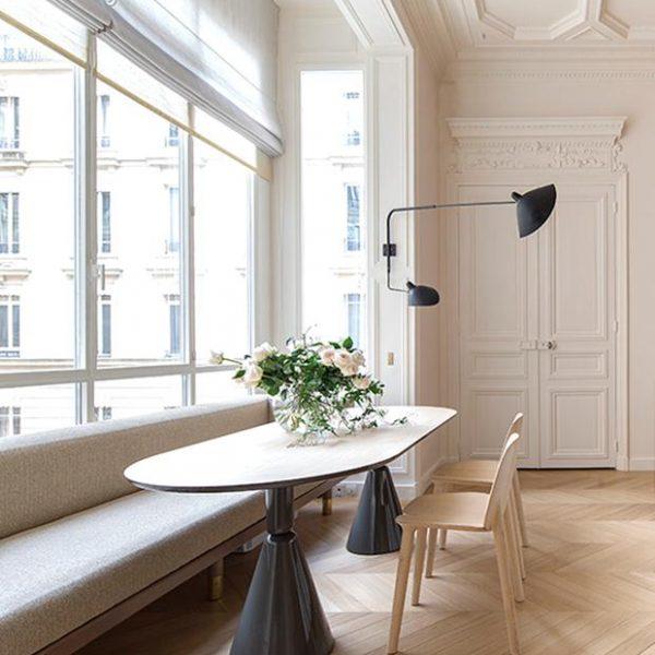 Piso em madeira em assentamento espinha de peixe, mesa ultra moderna e luminária Serge Mouille.