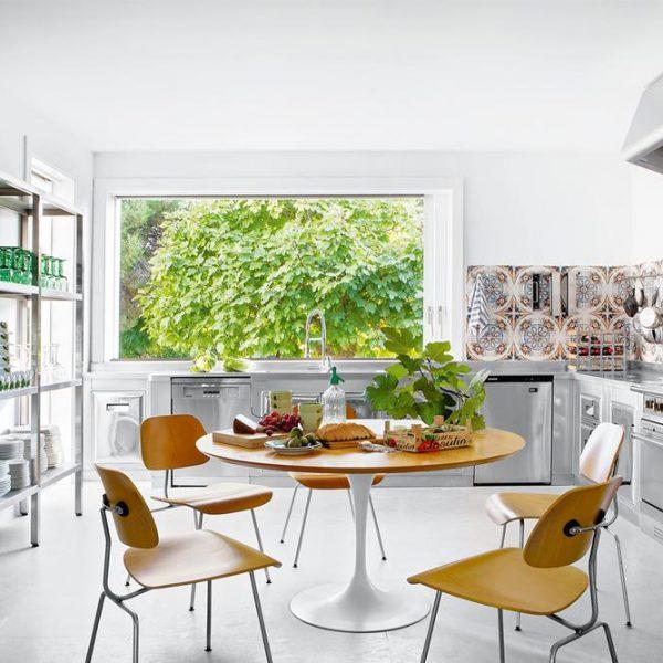 A louça fica à mostra na cozinha com pegada industrial em Marbella. Mesa de Eero Saarinen e cadeiras Plywood, do casal Eames