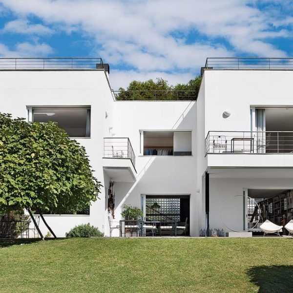 A fachada da casa de 600 m². Na varanda coberta, poltronas Coconut de George Nelson, da Vitra