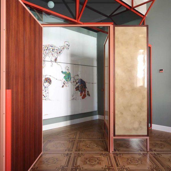 A estrutura em ferro pintada de vermelho delimita com delicadeza os espaços