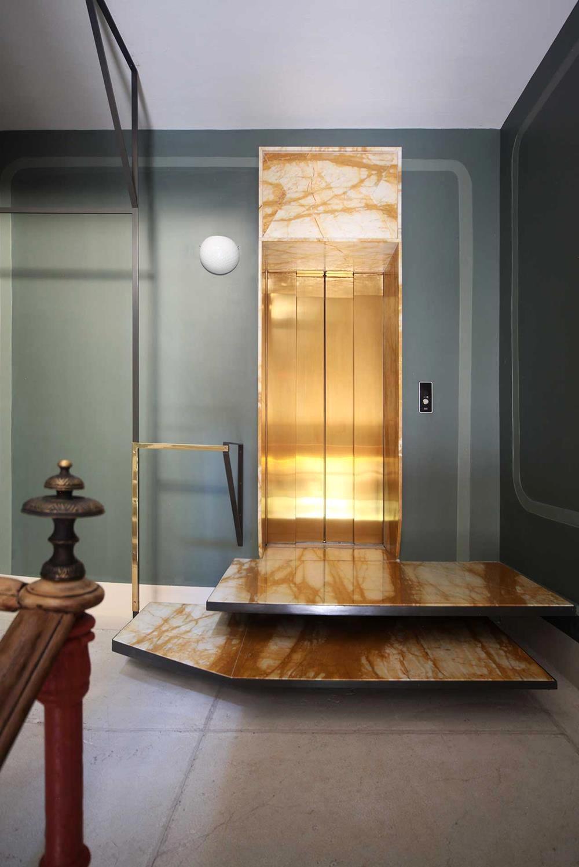 O glamour super moderno no elevador de portas douradas e escada em ângulos geométricos. Maravilhoso!