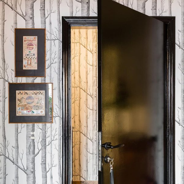 Porta preta e papel de parede descolado
