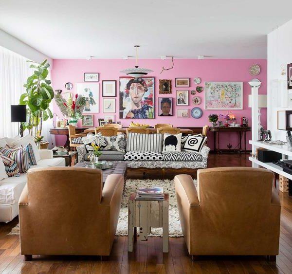 O living amplo abriga jantar e TV. O P&B é o contraponto à força da parede rosa