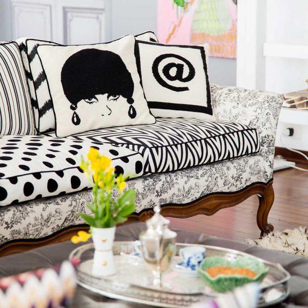 Sobre o sofá antigo revestido em tecidos estampados em P&B, almofada Jonathan Adler