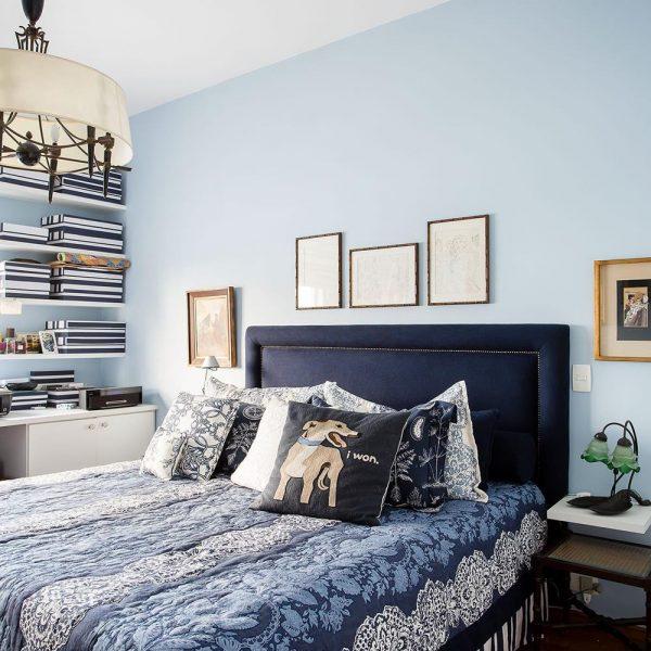 No quarto, parede azul em tom lindo, uma cor que fica bem praticamente na casa toda. Cama com cabeceira em veludo marinho e colcha em tons de azul