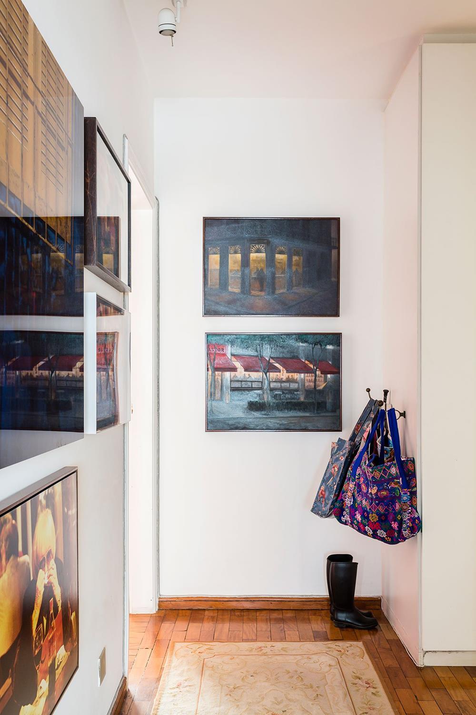 O corredor de acesso aos quartos recebe obras e espaço para bolsas e sapatos