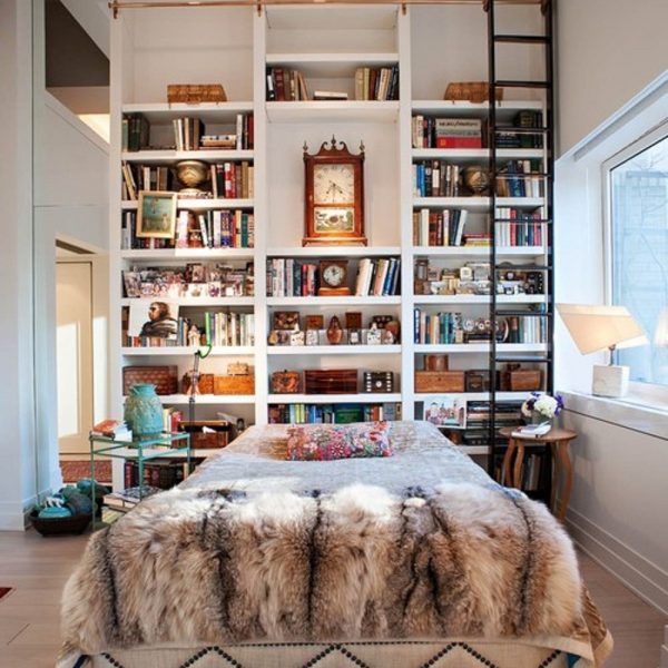 A cama solta deixa espaço para que a estante ocupe toda a parede e aproveita o pé direito alto