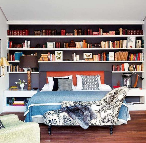 A estante contorna a cama, criando um nicho. Note que o tom mais escuro valoriza exemplares e adornos