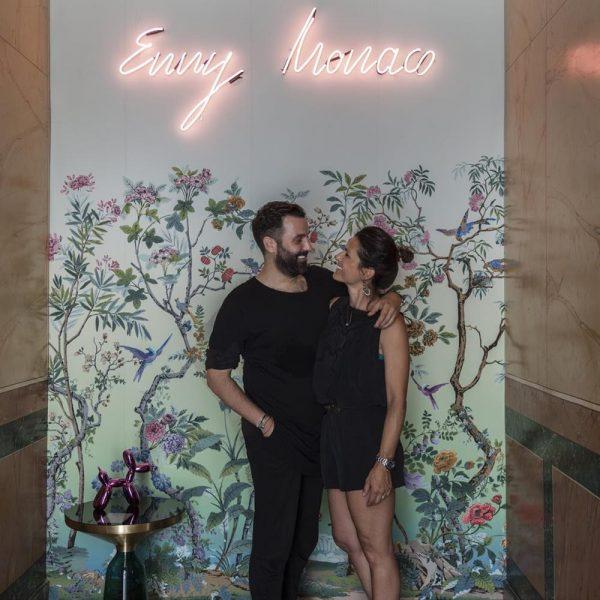 Curador e designer posam sob o neon com o nome da marca