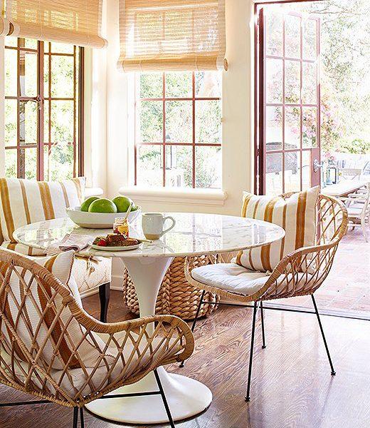 A mesa Saarinen branca, um super clássico, faz par esperto com as cadeiras em fibra e sofá revestido de tecido listrado