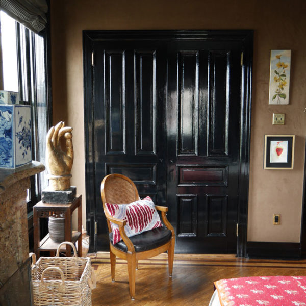 A porta laqueada em preto faz par com mobília e objetos de vários estilos, em perfeita harmonia
