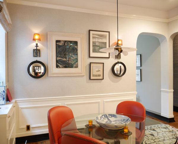 A sala de almoço recebe pintura bem clara, quase branca, que contrasta com as cadeiras em couro laranja