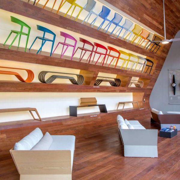 Uma parede inclinada rasgada com nichos retro iluminados, como uma onda, é a galeria que expõe pela primeira vez diversos produtos da Indio da Costa Design