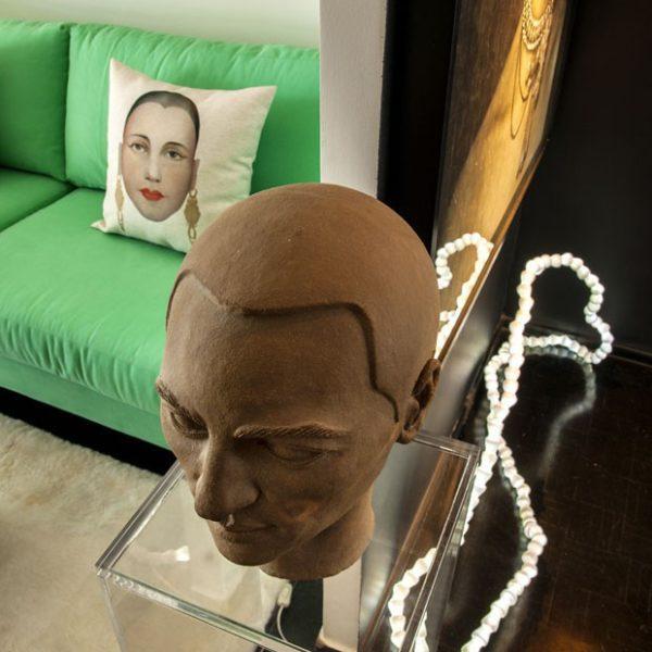 Escultura de Florian Raiss sobre coluna de acrílico. Crovato conta que mobiliário de acrílico é um de seus truques para pequenos espaços