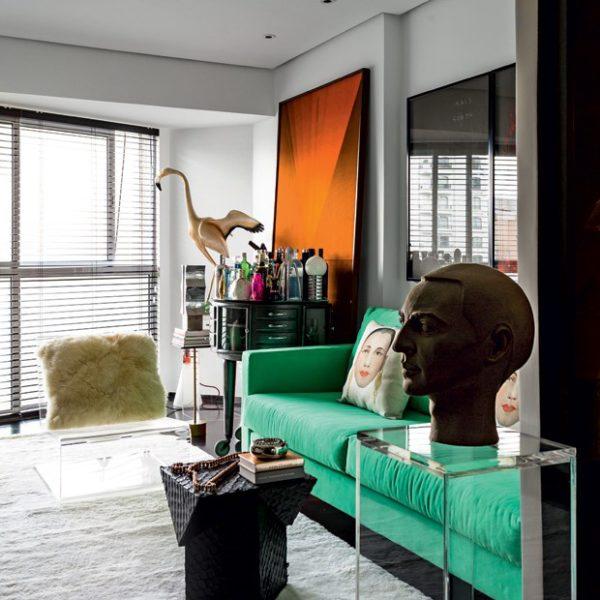 Em primeiro plano, escultura de Florian Raiss. Sofá de sarja verde da JRJ. Ao lado, tela de tecido de Verner Panton. Sobre o tapete By Kamy, banco Prisma, de pele de pirarucu, de Zanini de Zanine