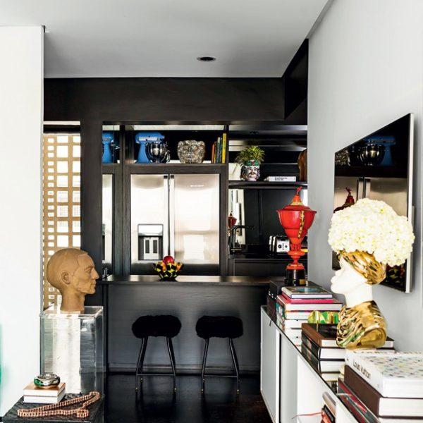 Integrada à sala, a pequena cozinha tem bancada americana. Sobre o rack da sala, escultura de cabeça em vaso Fornasetti Vintage 70's, com arranjo de Nelson Quionha