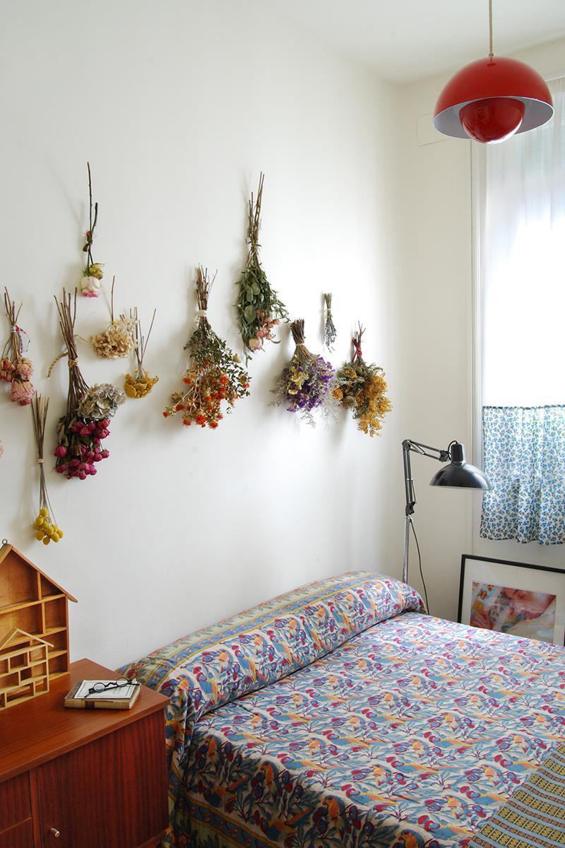 Flores secas em maços fazem bonito na principal parede do quarto, super em sintonia com a colcha, delicada e feminina