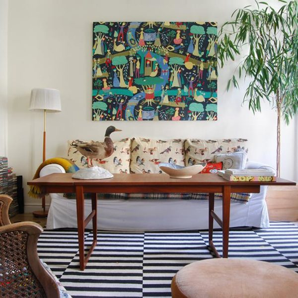 O living recebe sofá confortável com encostos revestidos em tecido diferente e divertido