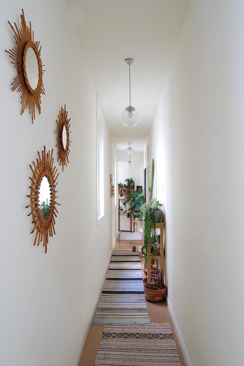 O corredor, bastante estreito, recebe na parede espelhos em fibra natural no formato de sol. No piso, tapetes sobrepostos, solução que se repete em todo o apartamento