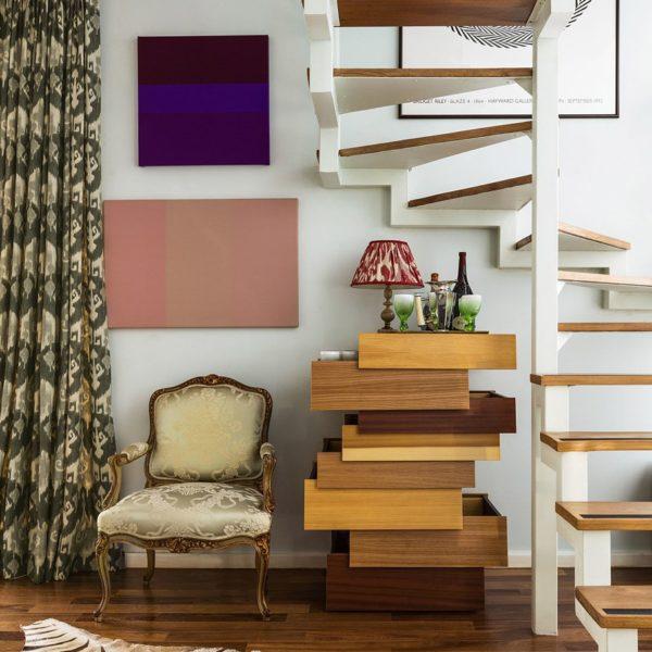 Poltrona italiana do século XIX sob a escada ao lado de cômoda de Raw Edges e Shay Alkalay. As obras são de Estela Sokol, e cartaz de Bridget Riley