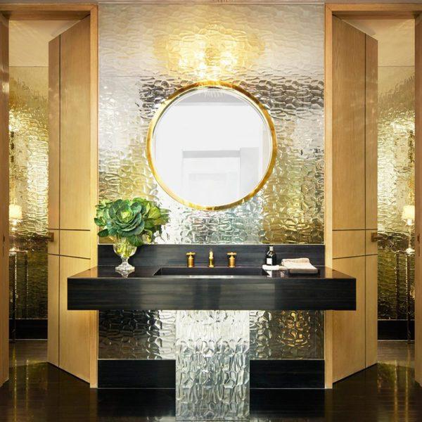 No banheiro, mármore e luminária Kelly Wearstler