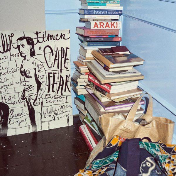 Bolsas Hermès e Comme des Garçons perto de uma pilha de livros